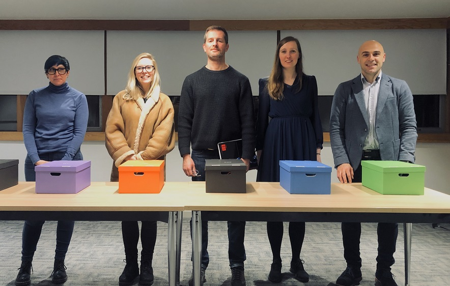 5 people standing behind a table with coloured shoeboxes on