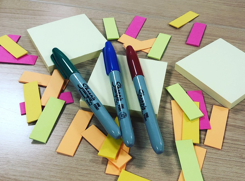 A pile of post-it notes and sharpie pens on a table