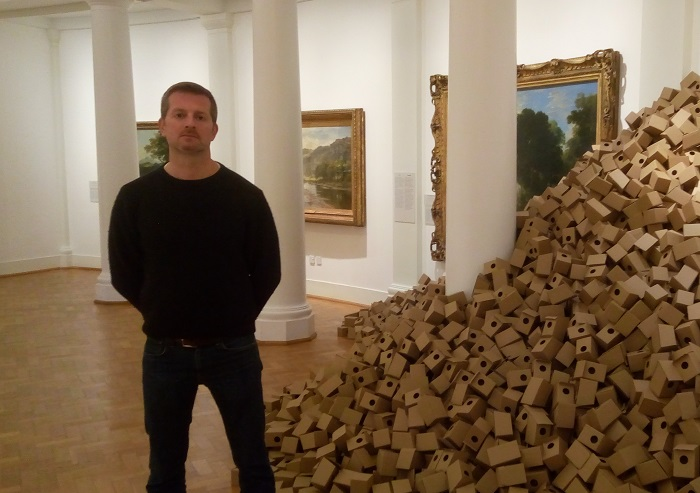 A man standing in a gallery near a sculpture made of a stack of boxes