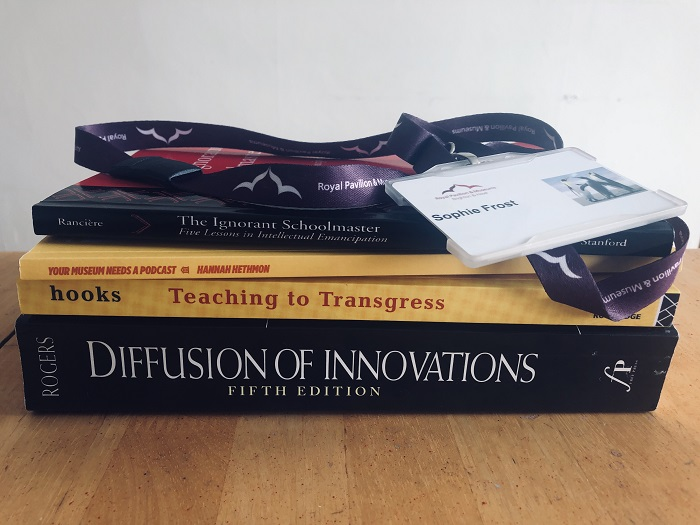 Sophie Frost's Brighton Museums nametag on a lanyard on top of a stack of textbooks