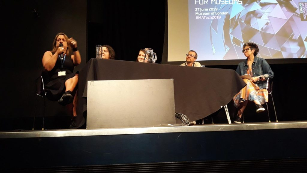 A panel of 5 people sitting on a stage