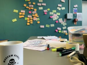 A mug labelled Museum Rebel on a desk in front of a green wall covered in post-it notes