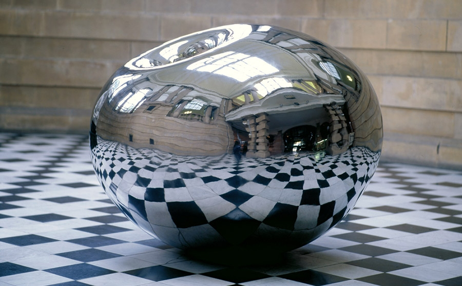 A reflective mirrored sculpture inside a historic hall with a black and white chequered floor
